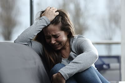 woman holding head and crying in need of anxiety treatment in new jersey from victory bay recovery